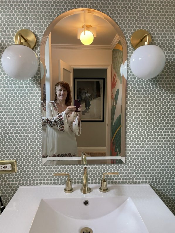white woman in a white dress taking a selfie in the remodeled bathroom.