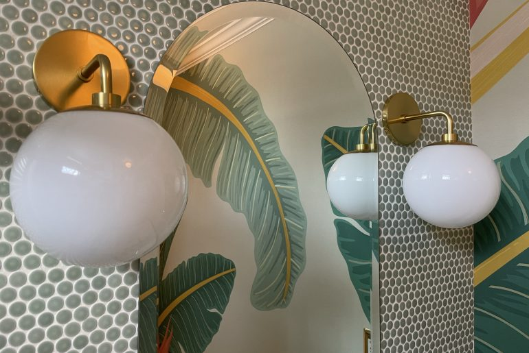 Close up of midcentury brass and white globe wall sconces against green penny tile. A reflection of palm wallpaper is an arched mirror.