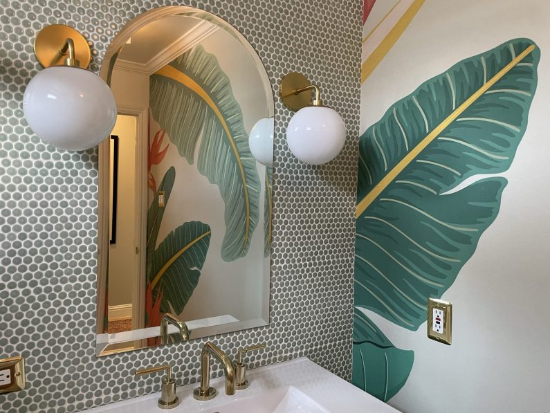 Modern tropical bathroom with green penny tile and palm frond wallpaper.