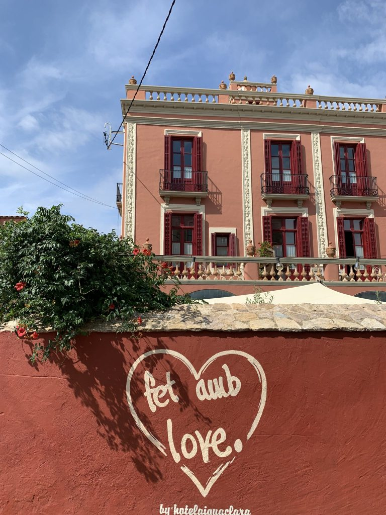 Charming antique hotel facade with a mural in Catalan reading made with love.