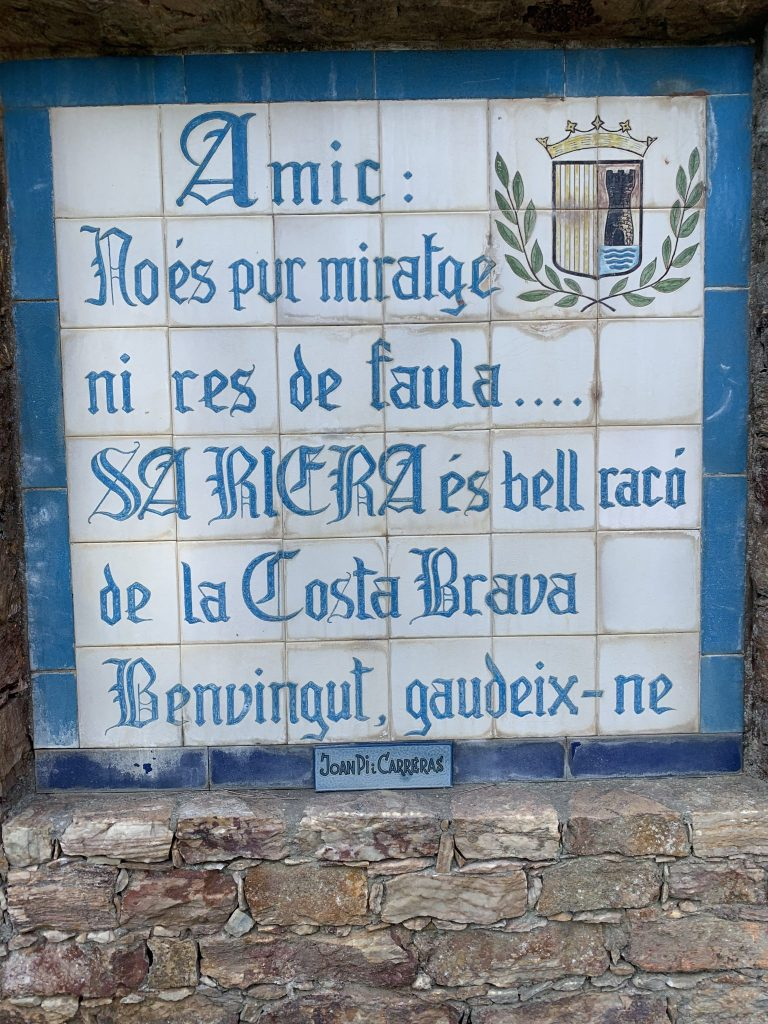 A tile sign written in Catalan welcoming visitors to the beachside village of Sa Riera.