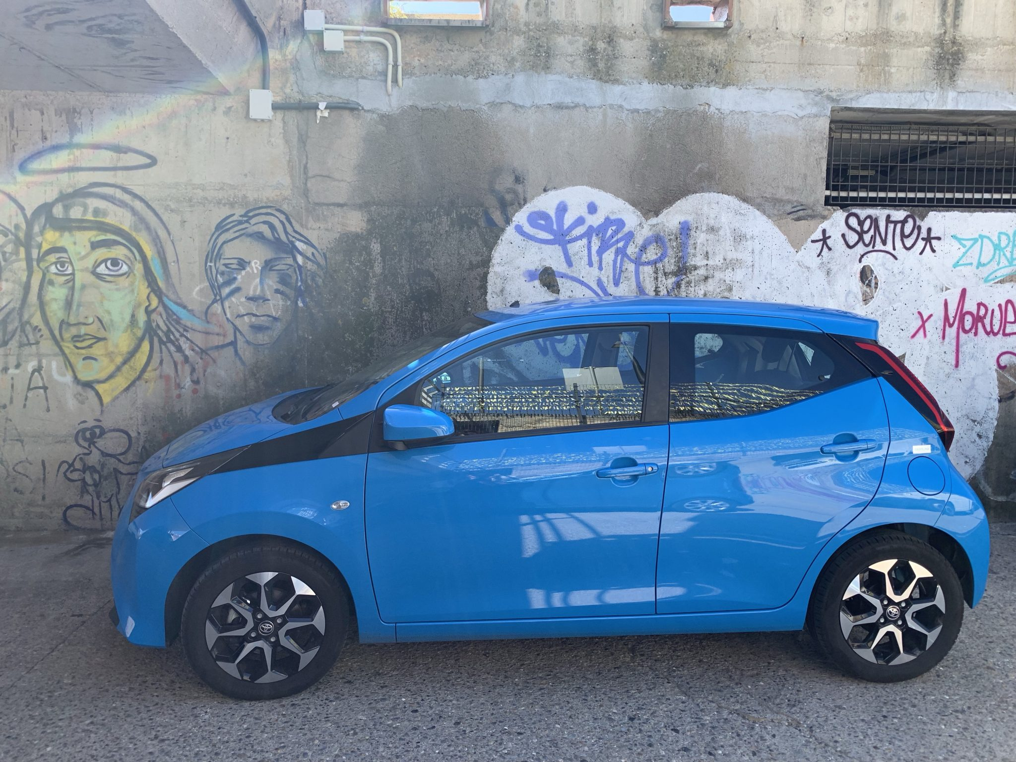 Small blue car in front of graffiti wall.