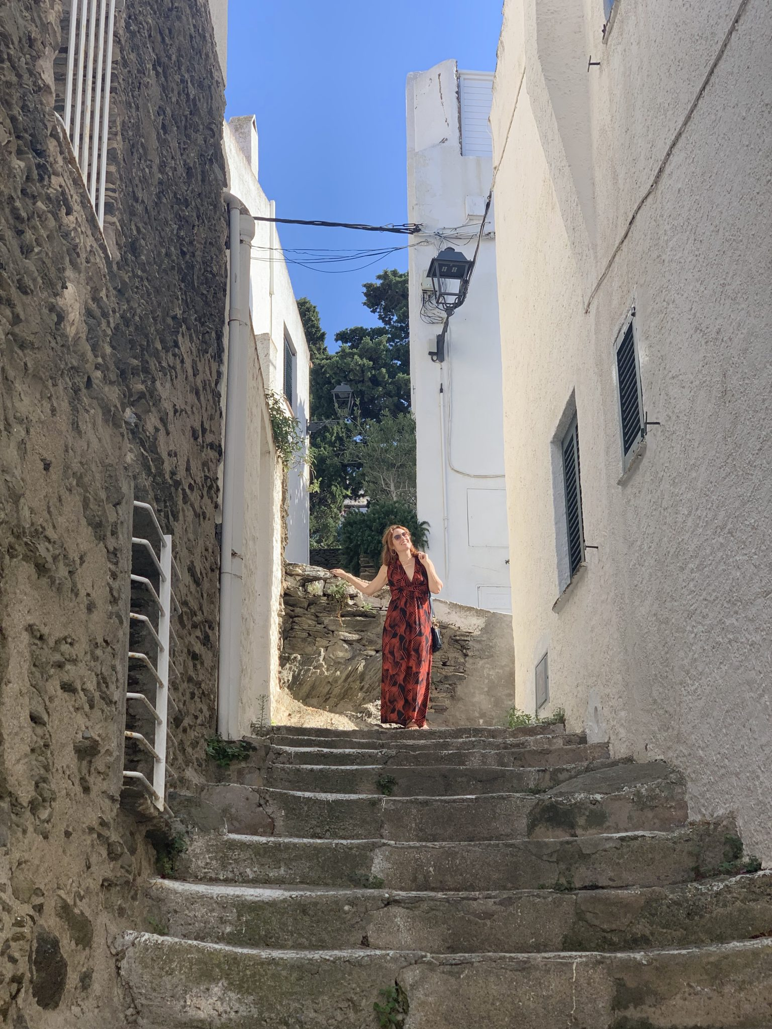 Woman stands on top of narrow street stairs wearing a red dress.