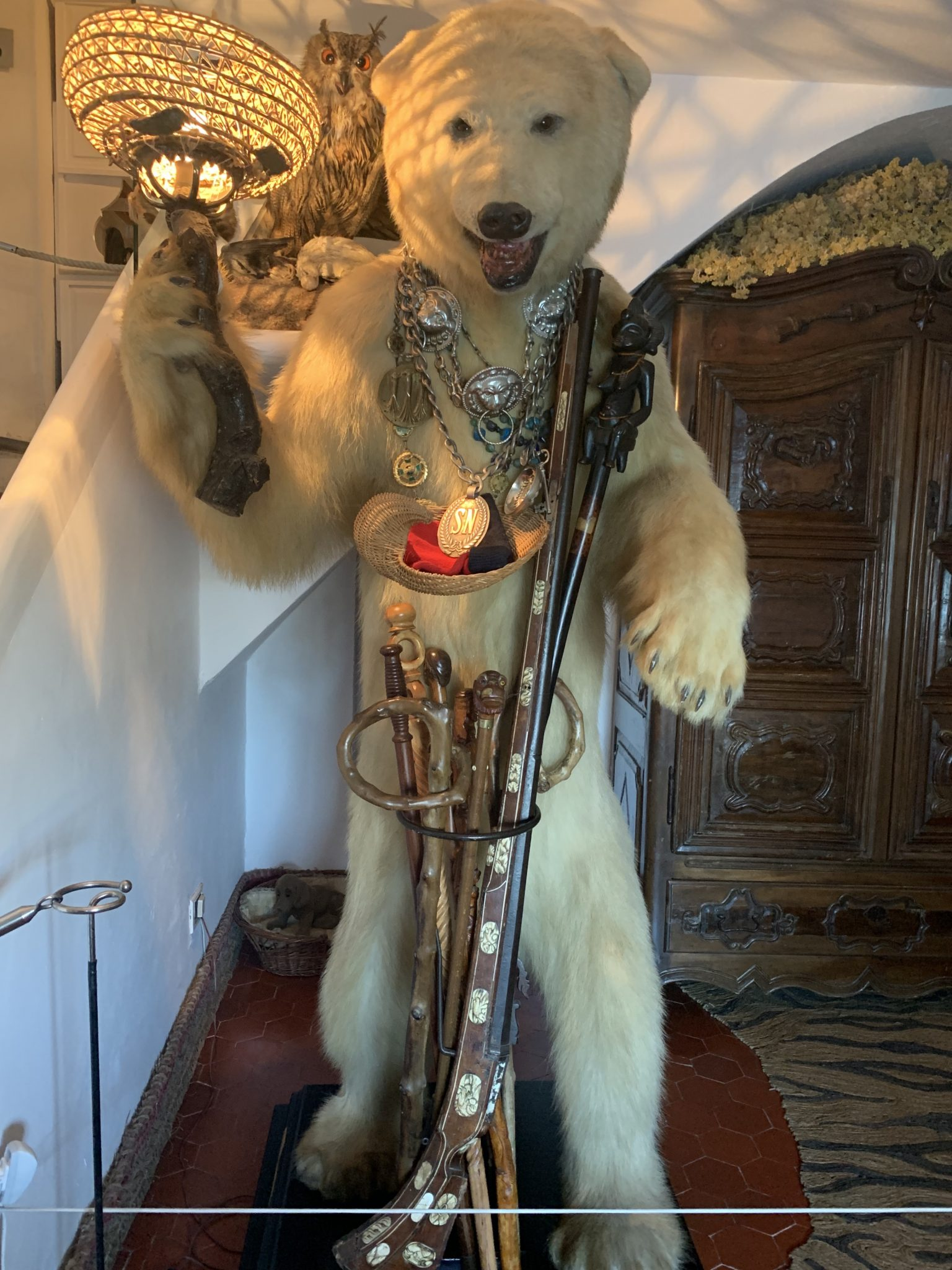 Stuffed polar bear decorated with swords and medals in the entryway to Dali's house.