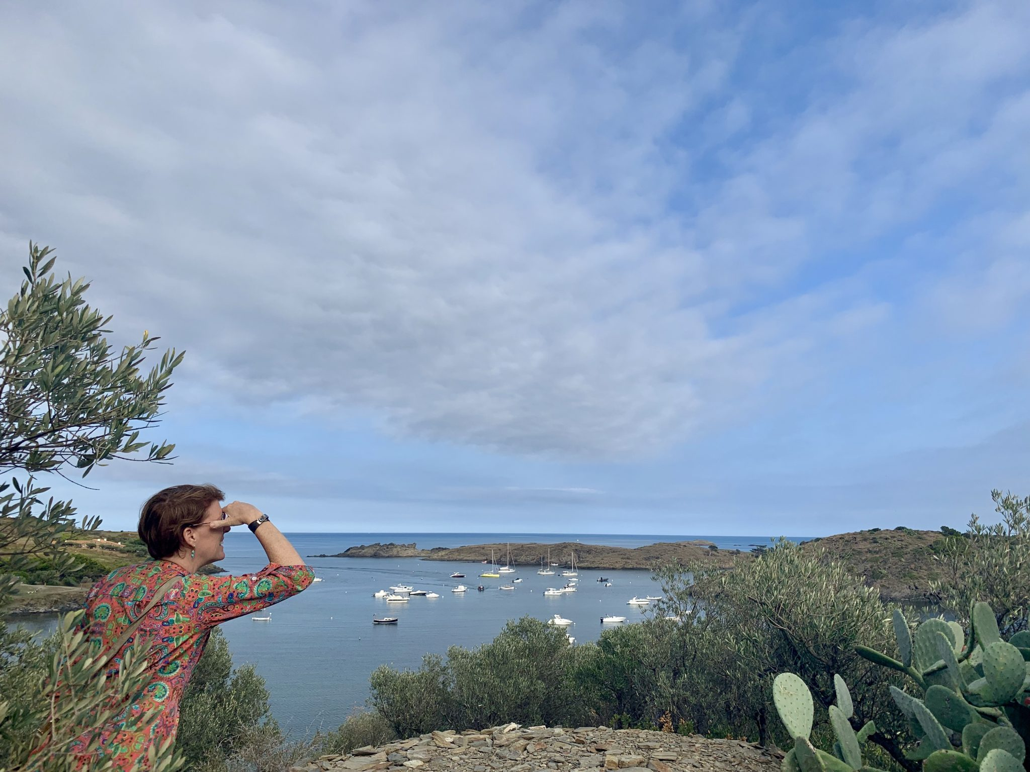 Woman looks out over bay of Portlligat.