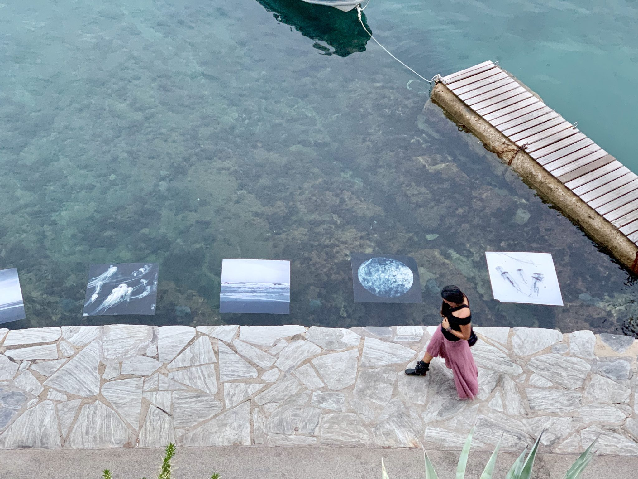 Woman walking past photography prints suspended in the sea as part of an art exhibit.