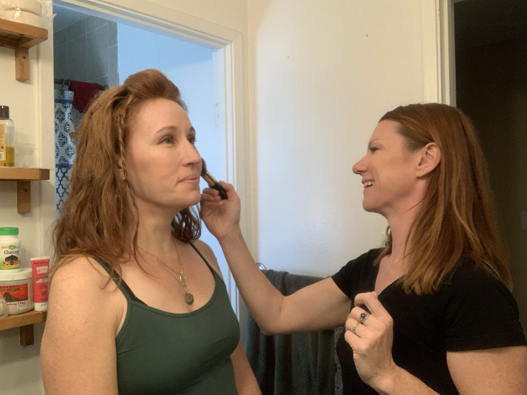 Two redheads with fair skin standing in a bathroom. One woman is smiling and applying blush to a second smiling woman.