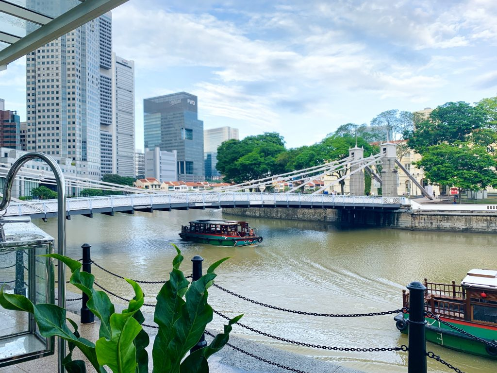 View of tug boats and Cavenagh Bridge over canal in Singapore.