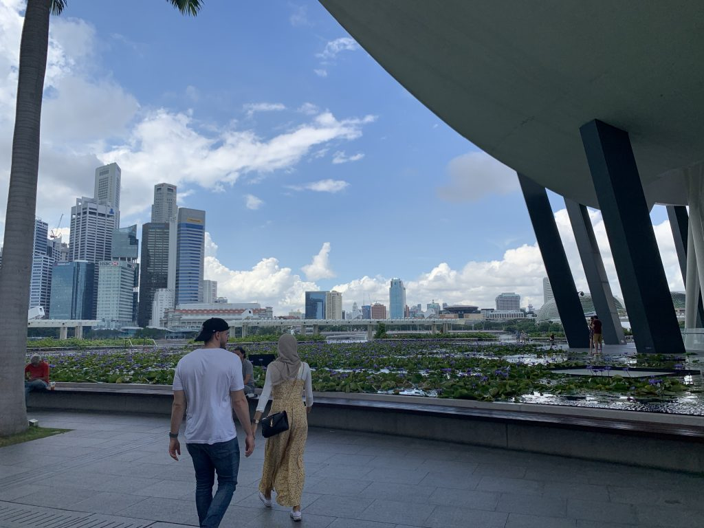 Singapore city skyline with a man in a white shirt and a woman wearing a yellow dress and hijab.