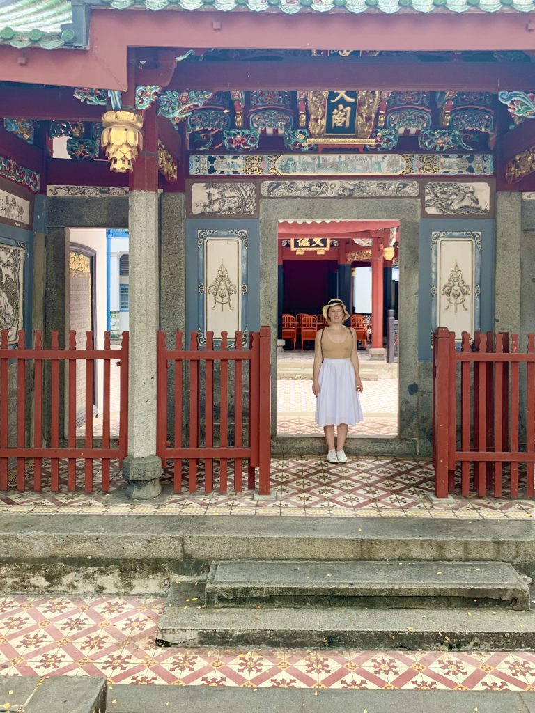 Woman standing in Chinese Buddhist Temple doorway, smiling.