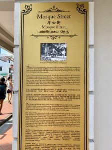 A written sign explaining the history of Mosque Street in Singapore