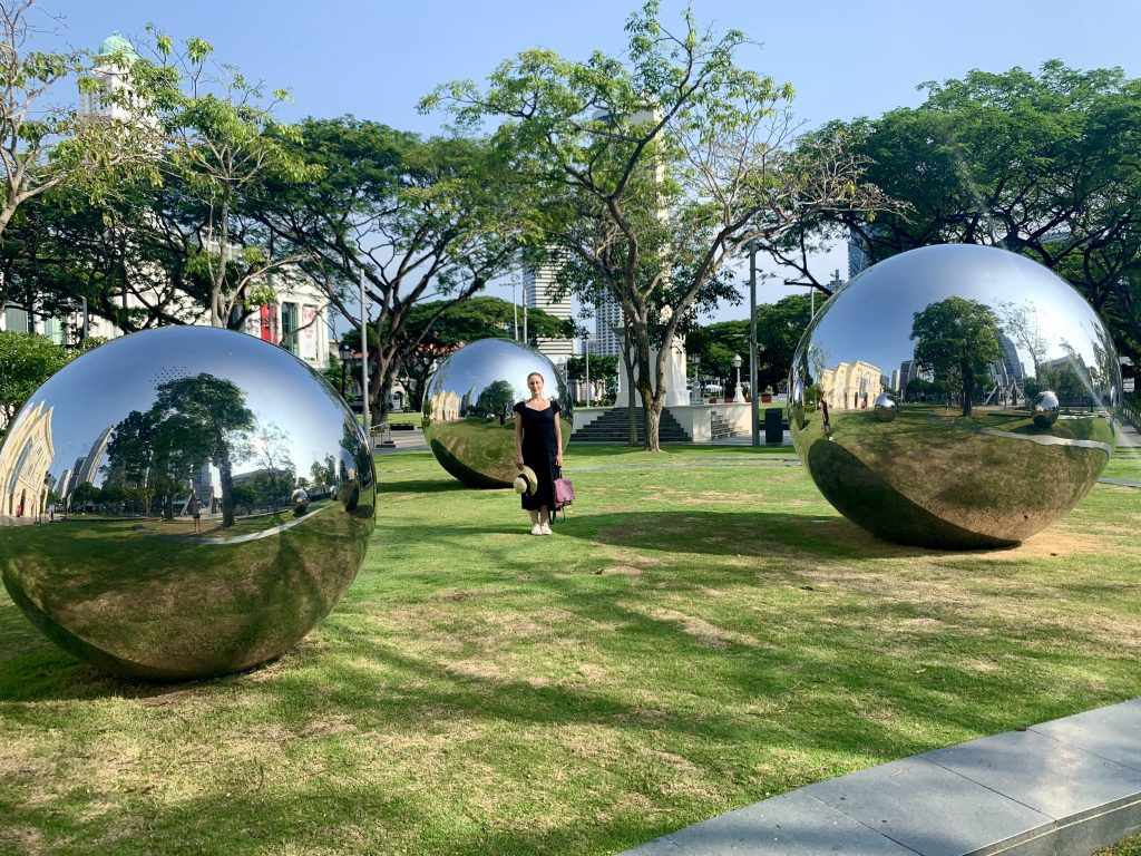 Woman standing in front of reflective sculptures