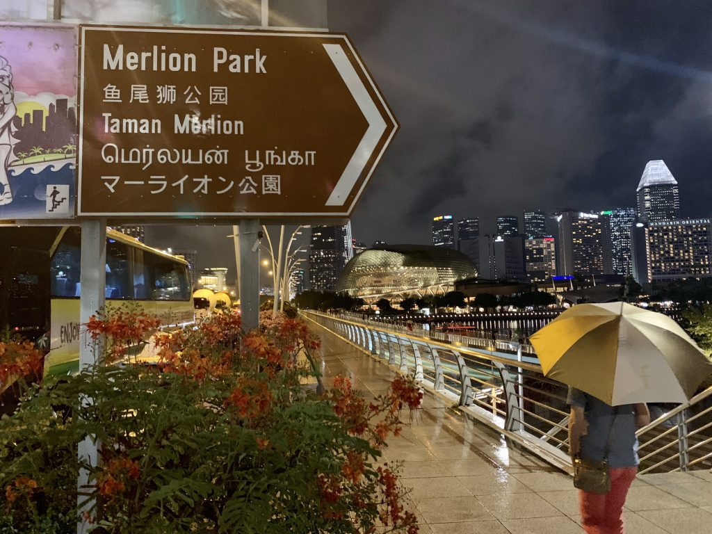 Rainy night, woman walking with umbrella under a sign reading Merlion Park