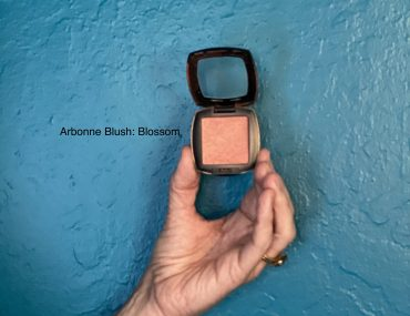 A photo of the Solstice blush for redheads, one with a powder brush on a dark bathroom counter and one held up to the teal wall.