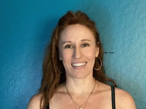 headshot of annie smiling wearing silver hoops, long red hair down with a small braid. She is wearing werk, a blush for redheads by Milk