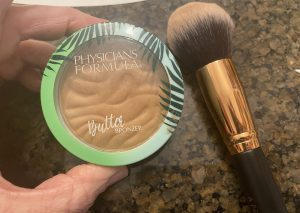 Phsyician's Formula Butter Bronzer with a powder brush against a marble counter.