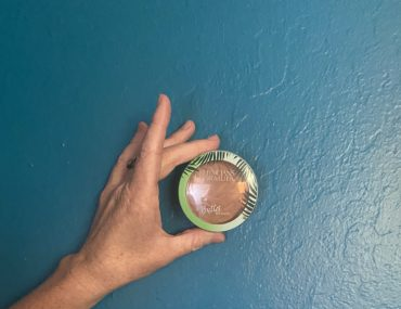 The bronzer held up by Annie's white, reddish hand against the teal wall.