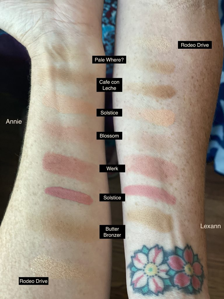 Two pale skin white under forearms with swatches of each of the 7 blush and bronzer colors labeled with overlaid text. Lexann's arm on the right has a double flower tattoo.