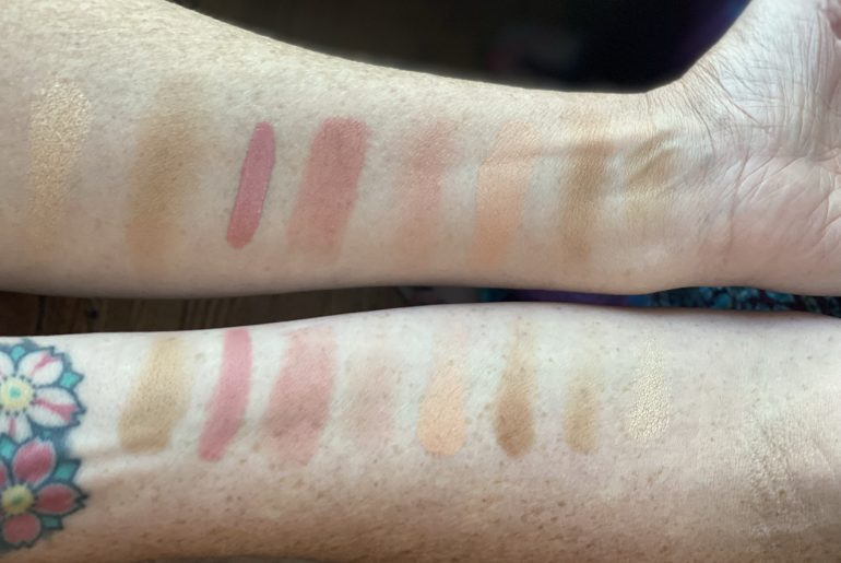Two pale white arms with seven swatches of blush and bronzer
