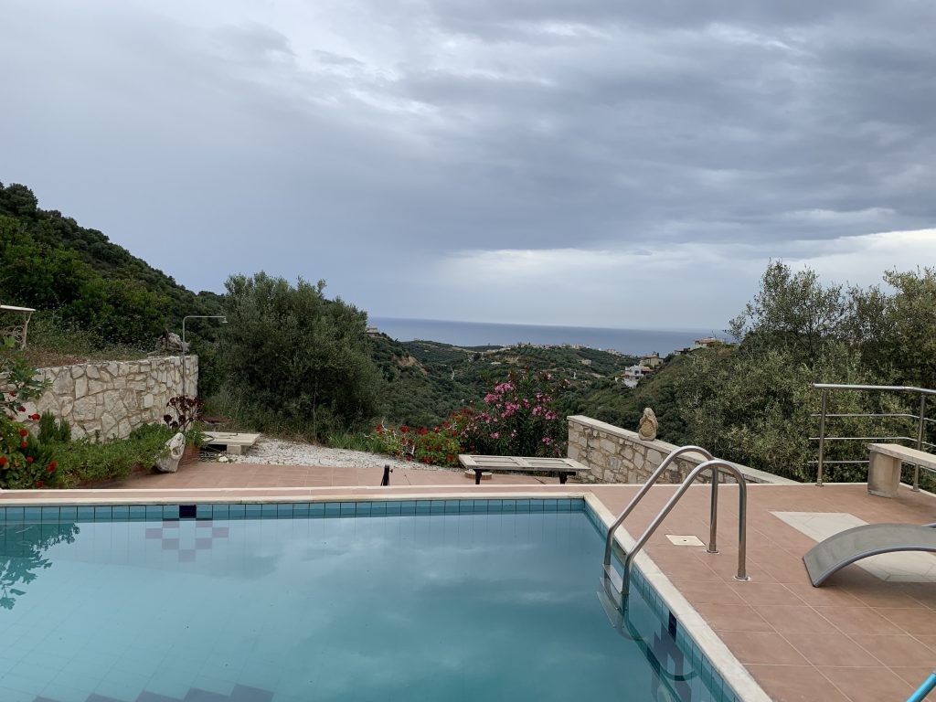 view over a swimming pool looking out toward the sea with a cloudy sky behind